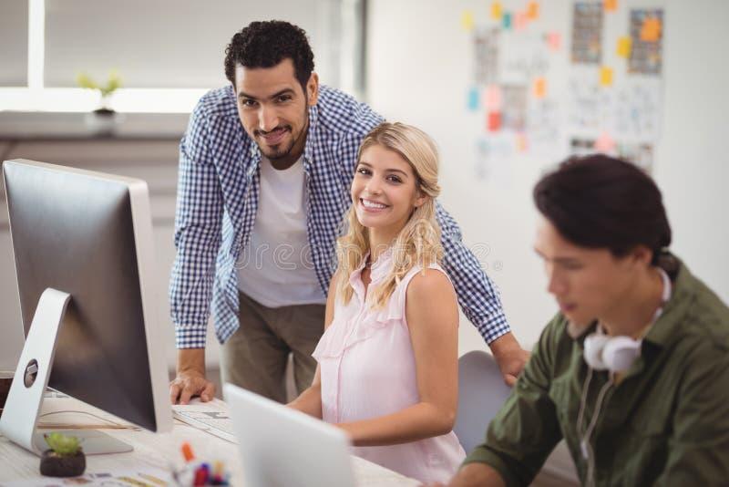 工作在台式计算机的年轻企业同事画象在办公桌 库存照片