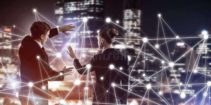 工作在合作的社会连接和网络的概念反对夜城市视图和伙伴 免版税库存图片