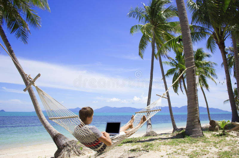 工作在吊床的一台膝上型计算机的商人在海滩天蓝色海 免版税图库摄影