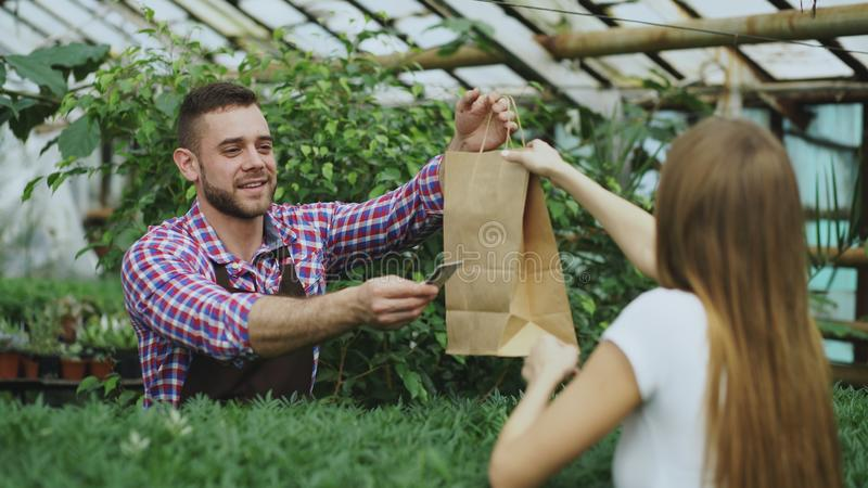 工作在园艺中心的年轻微笑的卖主卖花人 人给购物袋顾客和制造付款由信用 免版税库存图片