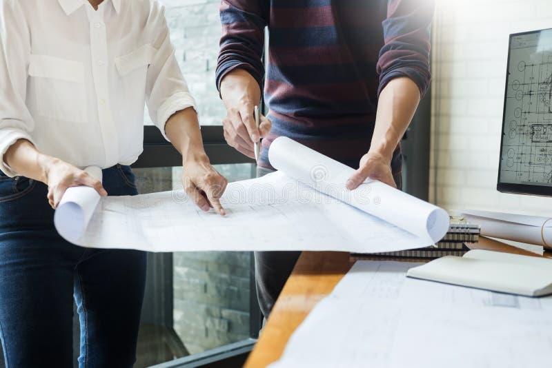 工作在图纸的专业建筑师谈论construc 库存照片