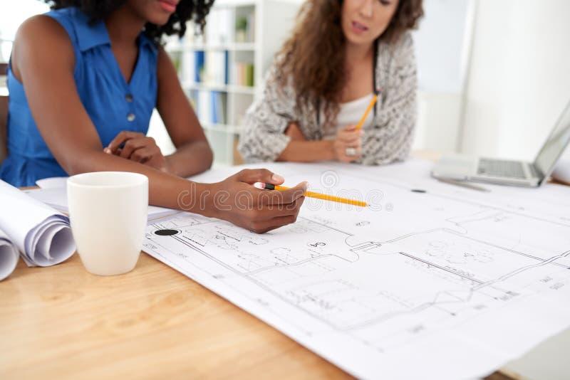 工作在图纸的女性工程师 免版税图库摄影