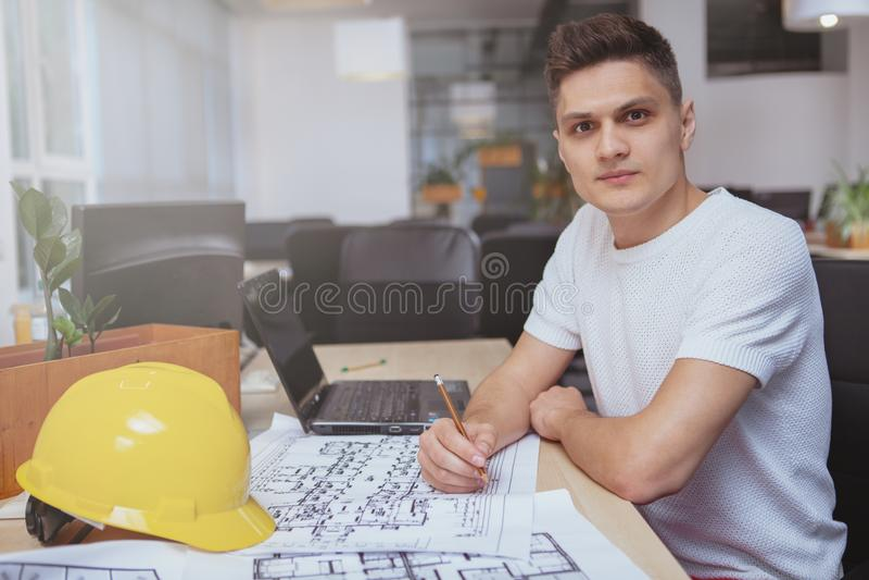 工作在图纸的成功的建筑师在办公室 图库摄影