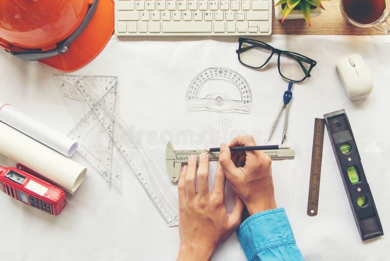 工作在图纸的顶视图建筑师 建筑师工作场所 工程师工具和安全控制,图纸,统治者,橙色舵 免版税库存照片