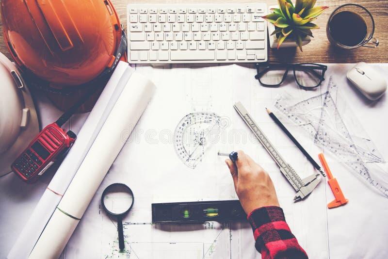 工作在图纸的顶视图建筑师 建筑师工作场所 工程师工具和安全控制,图纸,统治者,收音机,膝上型计算机 库存照片