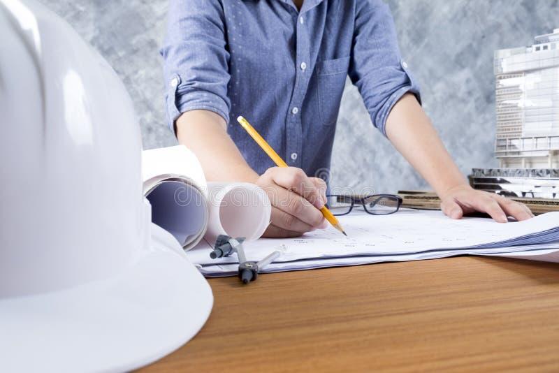 工作在图纸,建筑和设计概念的建筑师或工程师 免版税库存照片