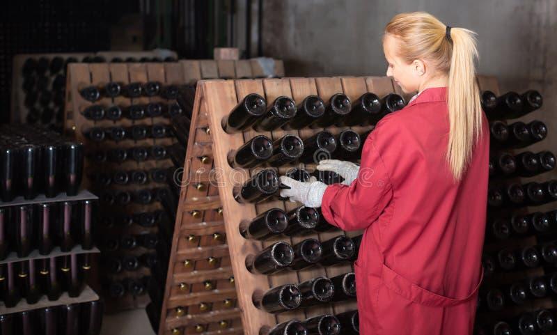 工作在地窖里的愉快的妇女酿酒厂雇员 免版税库存照片