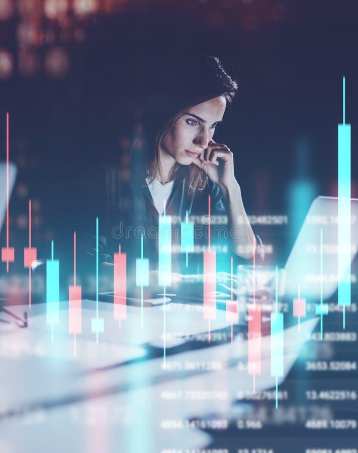 工作在夜现代办公室顶楼的年轻女人 红色和绿色烛台图和股票交易在背景 ? 库存照片