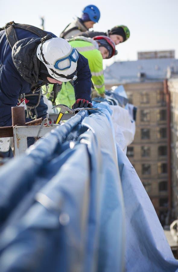 工作在大厦屋顶的工业登山人  免版税库存照片