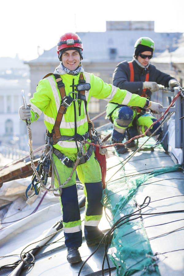 工作在大厦屋顶的工业登山人  免版税图库摄影
