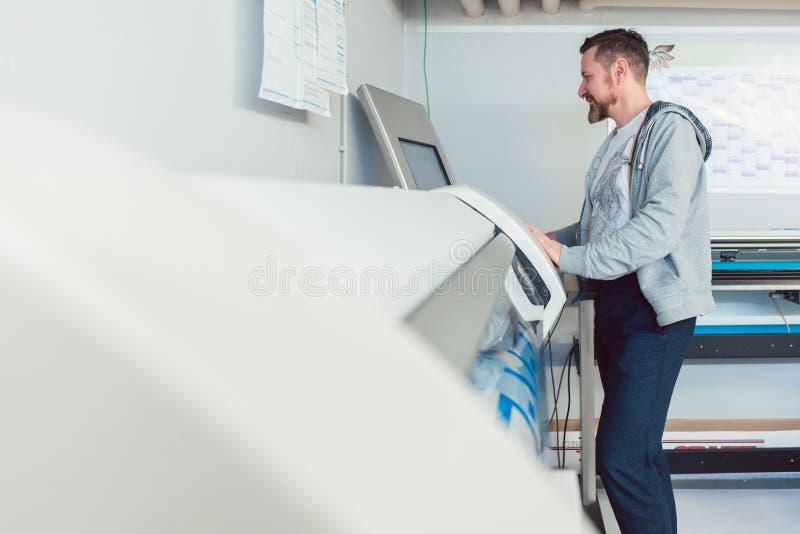 工作在大型格式化打印机的人在广告商中 免版税库存图片