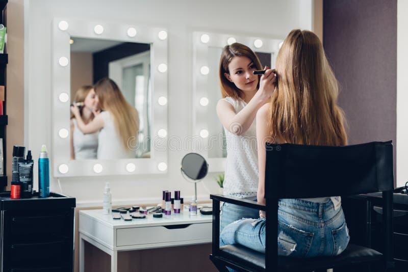 工作在女孩的专业化妆师创造自然神色在美容院 免版税图库摄影