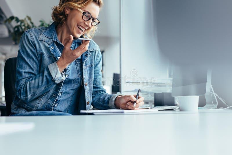工作在她的书桌的微笑的年轻女实业家 库存照片
