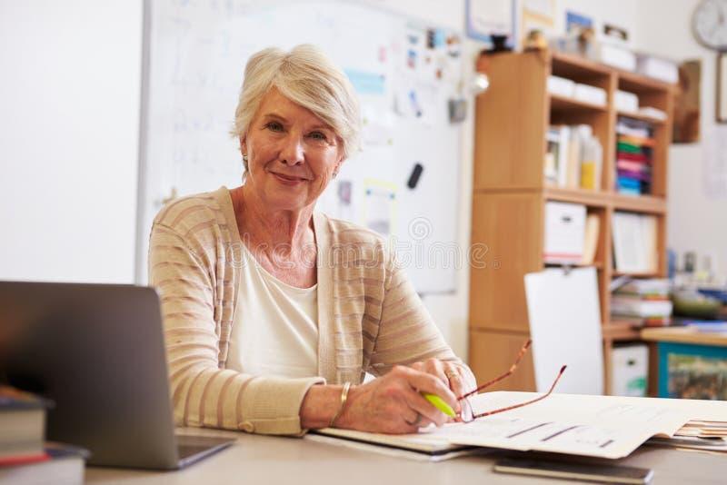工作在她的书桌的资深女老师画象  免版税库存图片