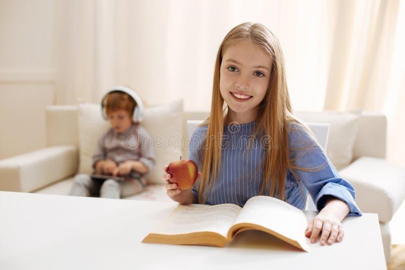 工作在她的家庭任务的坚持活跃女孩 图库摄影