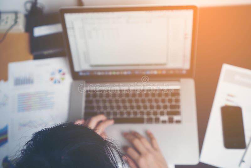 工作在她的有文件和膝上型计算机的办公桌的女商人 工作在纸的女实业家 库存照片