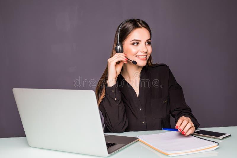 工作在她的有耳机和膝上型计算机的书桌的美丽的女商人画象在办公室 免版税库存照片