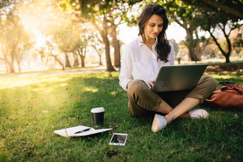 工作在她的笔记本的年轻女实业家在公园 在象草的草坪的自由职业者女性开会使用有她的日志的手提电脑 免版税库存照片