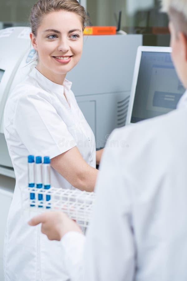 工作在实验室的微笑的妇女 免版税库存图片