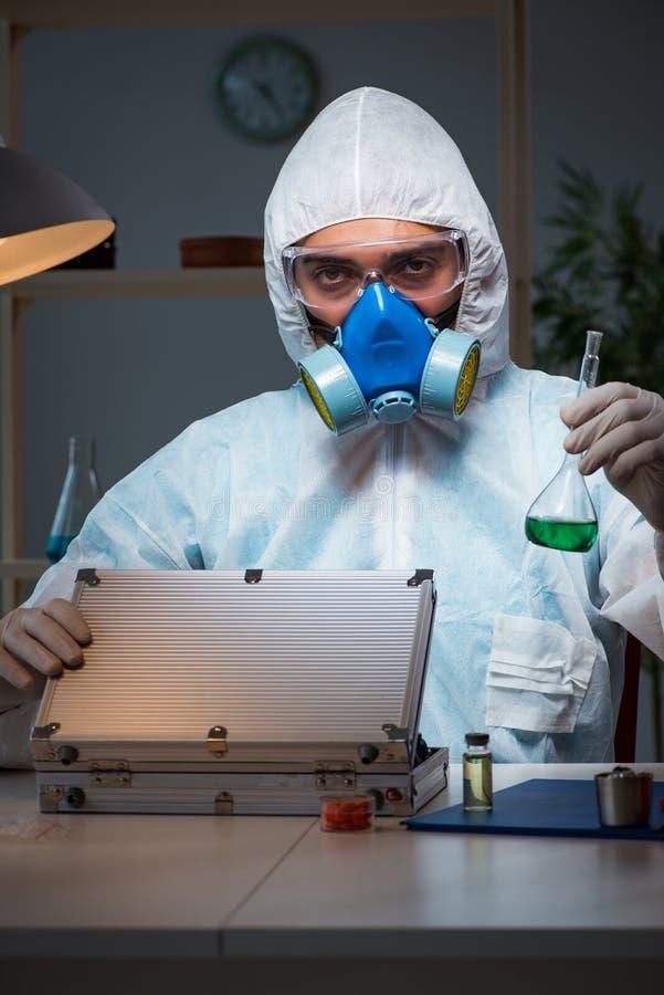 工作在实验室的法庭调查员寻找证据 免版税库存图片