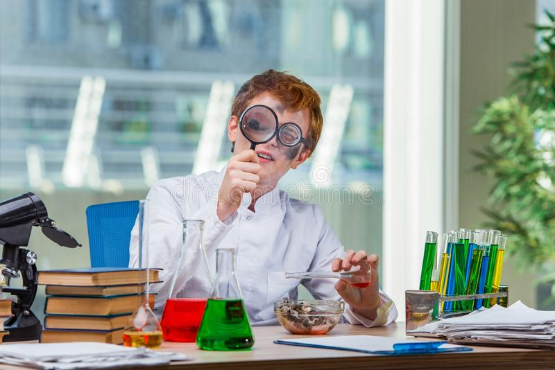 工作在实验室里的年轻疯狂的化学家 图库摄影