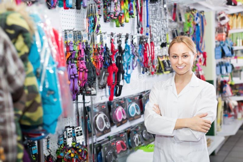 工作在宠物店的微笑的女性助理 库存照片