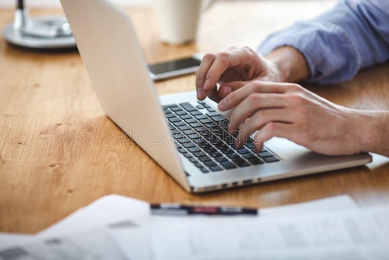 工作在家庭办公室的商人 供以人员坐的木桌和使用当代笔记本,发短信给消息键盘 库存图片