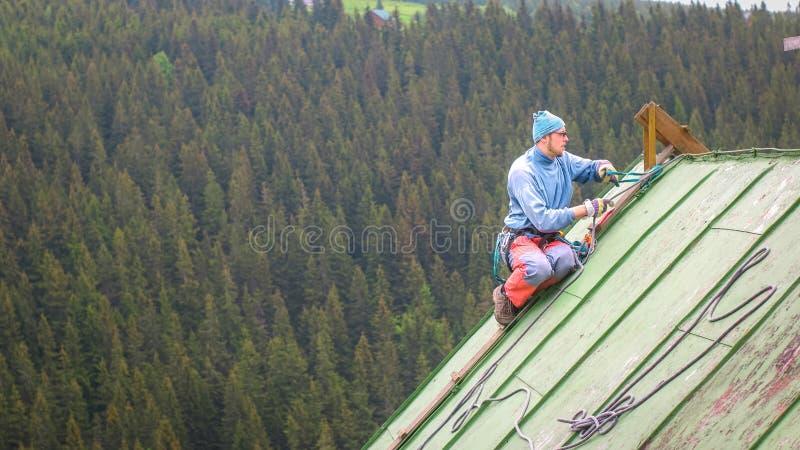 工作在屋顶的人,检查安全齿轮 免版税图库摄影