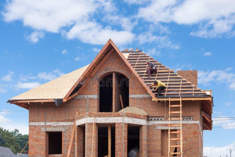 工作在屋顶覆盖的建筑队新房做用砖 免版税库存图片