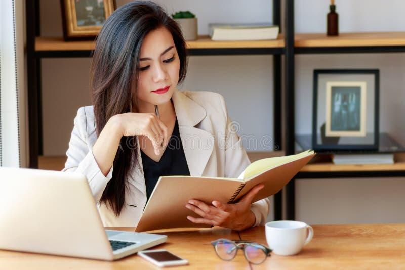 工作在工作场所的年轻亚裔女商人 偶然衣服的美丽的亚裔妇女与看书一起使用 库存图片