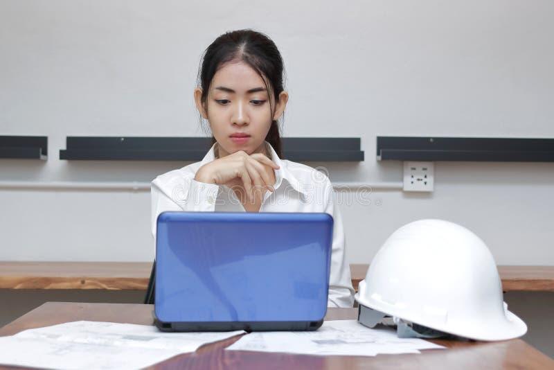 工作在工作场所的确信的年轻亚裔女实业家正面图在现代办公室 认为和浓缩周道的事务 免版税库存照片