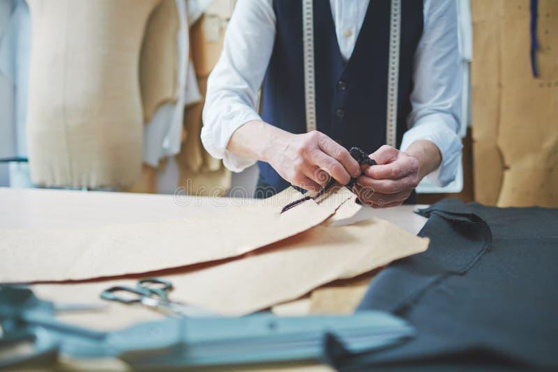 工作在工作室的熟练的裁缝