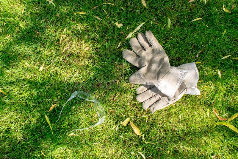工作在庭院、放置在绿草的防护手套和glases里 库存照片