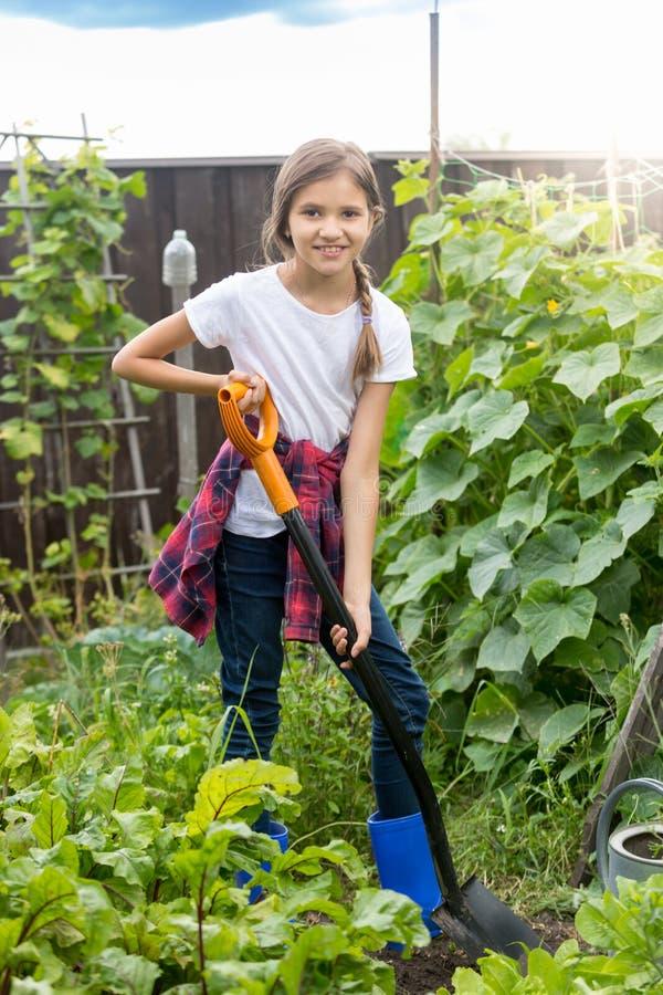 工作在庭院和开掘的土壤的逗人喜爱的十岁的女孩 库存图片