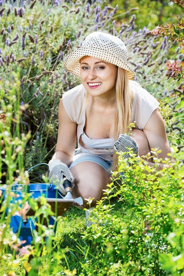 工作在庭院里的妇女使用在summe的园艺仪器 库存照片