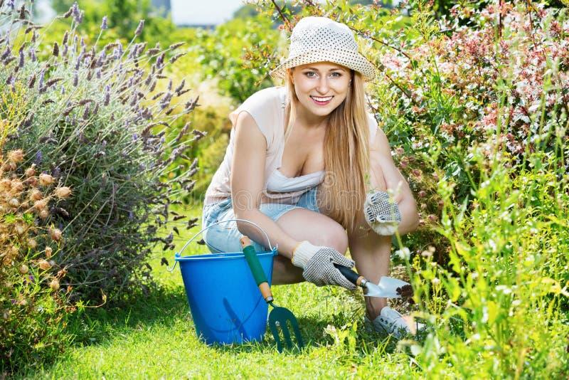工作在庭院里的妇女使用在summe的园艺仪器 免版税库存照片