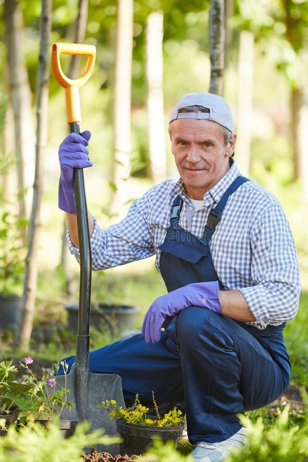 工作在庭院里的微笑的人 免版税库存图片