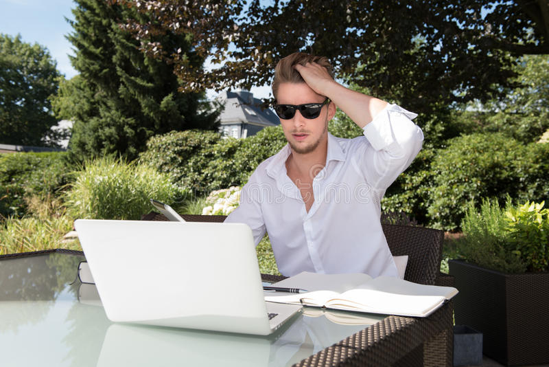 工作在庭院里的年轻英俊的商人 库存图片