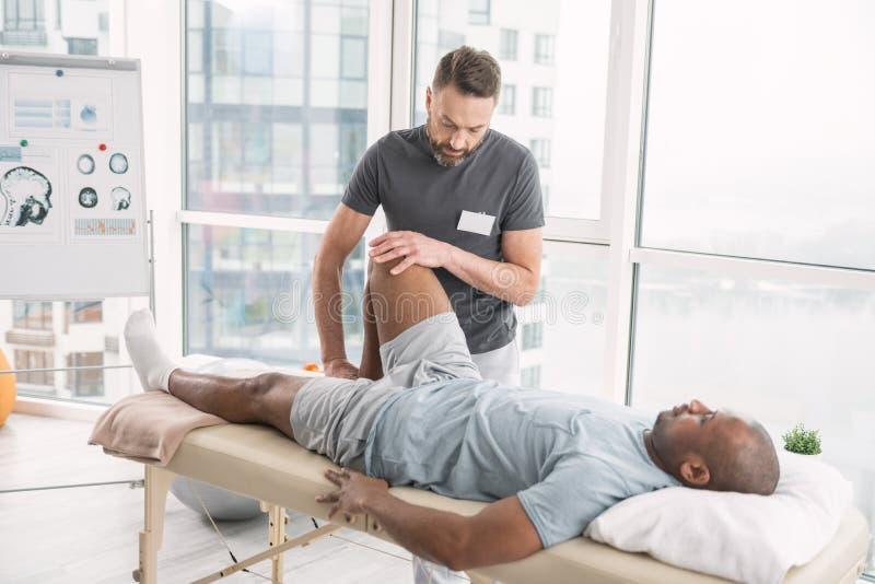 工作在康复中心的专业男性治疗师 库存照片