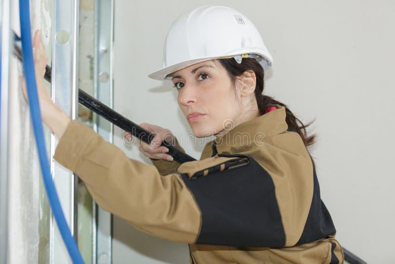 工作在建造场所的可爱的妇女工程师 免版税图库摄影