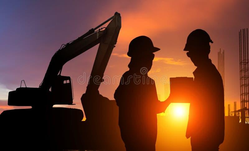 工作在建造场所的建筑工人在产业背景的日落 库存照片