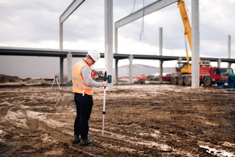 工作在建造场所的测量员工程师,与经纬仪和gps系统一起使用 免版税库存图片