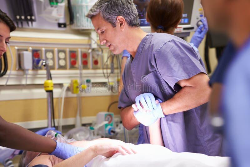 工作在患者的医疗队在急诊室 免版税图库摄影