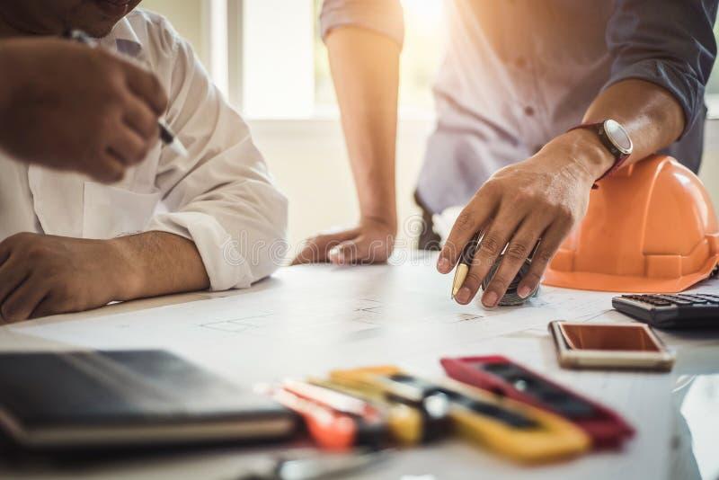 工作在房子图纸的工程师在谈论的不动产项目办公室 工程学工具和建筑概念 库存图片