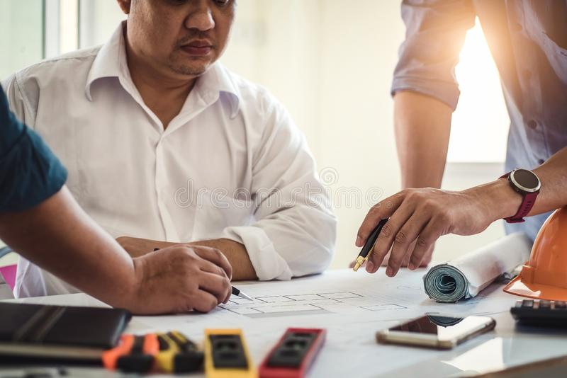 工作在房子图纸的工程师在谈论的不动产项目办公室 工程学工具和建筑概念 免版税库存图片