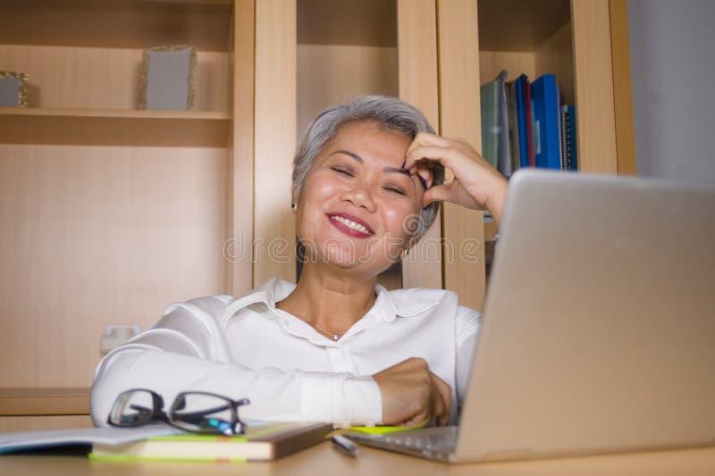 工作在手提电脑书桌微笑的可爱和愉快的成功的成熟亚裔妇女自然生活方式办公室画象  免版税库存照片
