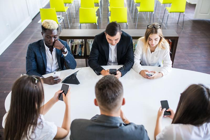 工作在手机的不同的办公室人民 拿着智能手机的公司雇员在见面 严肃多种族 免版税库存照片