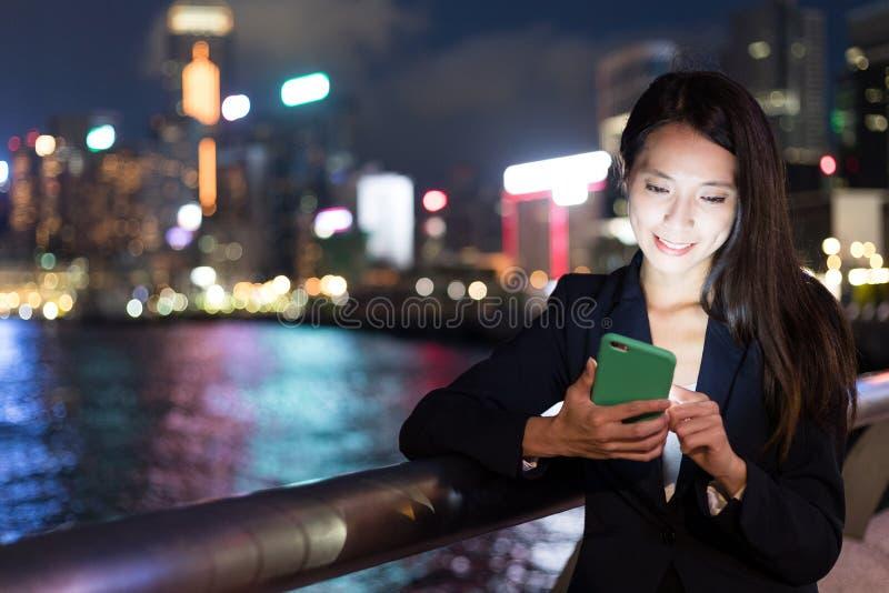 工作在手机的女商人在室外 图库摄影