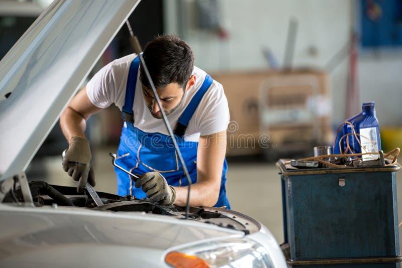 工作在敞篷下的汽车机械师 免版税库存图片