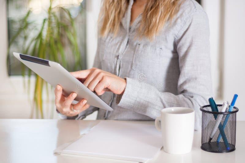 工作在数字式片剂的女商人在书桌在现代办公室 免版税库存照片